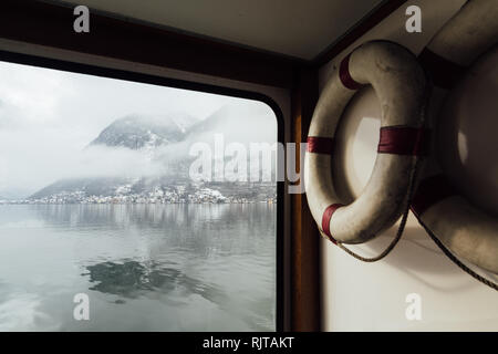 View over Hallstatt town and Alps mountains from inside the passenger lake ferry. Retro lifebuoy on the foreground. - Stock Photo