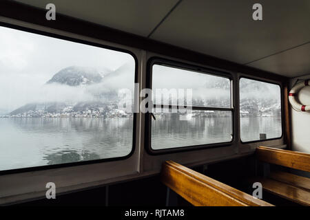 View over Hallstatt town and Alps mountains from inside the passenger lake ferry. Empty seats on the foreground. - Stock Photo