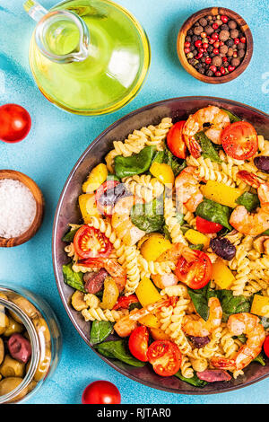 Fusili pasta salad with shrimps, tomatoes, peppers, spinach, olives, top view. - Stock Photo