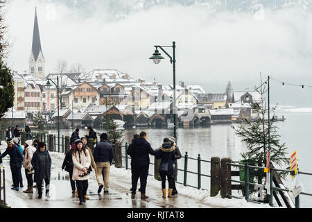 HALLSTATT, AUSTRIA - JANUARY 2019: tourists walking along the lake waterfront in the old town of Hallstatt with snowy mountains on the background. - Stock Photo