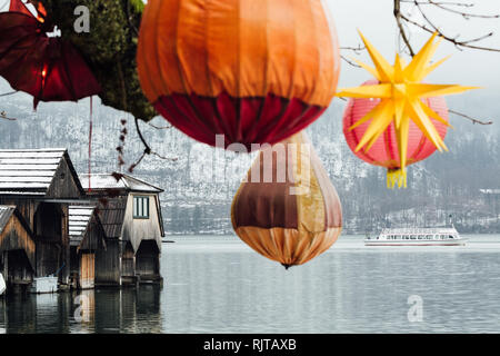 HALLSTATT, AUSTRIA - JANUARY 2019: lake ferry passing the wooden boat houses of Hallstatt old town. Christmas lights on the foreground. - Stock Photo
