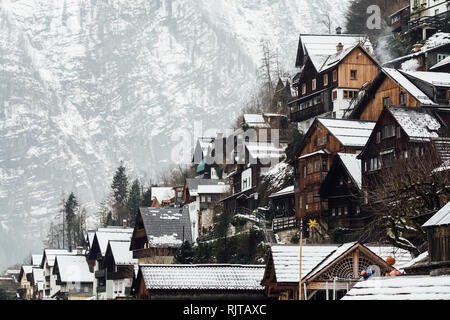 HALLSTATT, AUSTRIA - JANUARY 2019: view over wooden houses of old town and Alps mountains after snow storm. - Stock Photo