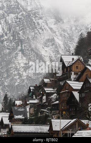 HALLSTATT, AUSTRIA - JANUARY 2019: view over wooden houses of old town and Alps Mountains after snow storm. Vertical orientation. - Stock Photo