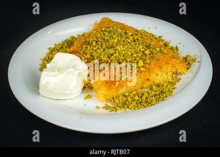 Traditional Turkish Dessert Kunefe isolated on black. - Stock Photo