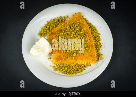 Traditional Turkish Dessert Kunefe isolated on black. - Stock Photo