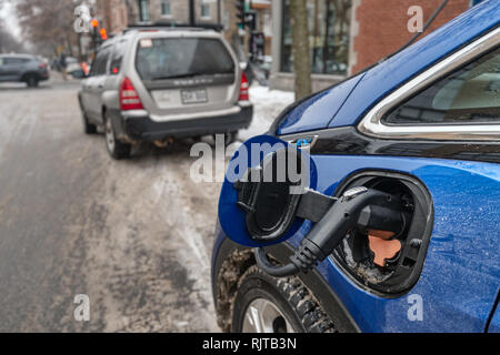 Montreal, Canada - 7 February 2019: Electric car plugged in and charging in the wintertime on Gilford Street. - Stock Photo