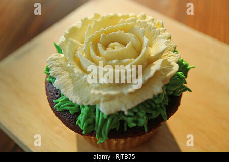 Closed up a chocolate cupcake decorated with rose flower shaped whipped cream isolated in sunlight - Stock Photo