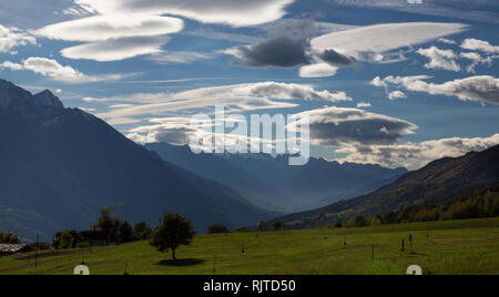 View over The Alps from the village St. Denis, northern Italy. The many rare shaped clouds in the sky are being illuminated by the sun - Stock Photo