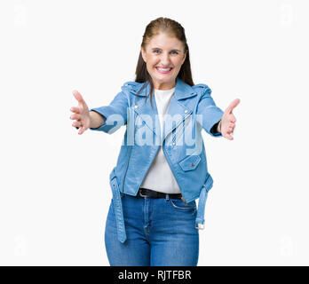 Beautiful middle age mature woman wearing fashion leather jacket over isolated background looking at the camera smiling with open arms for hug. Cheerf - Stock Photo