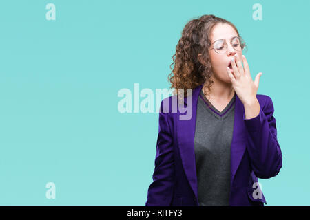 Young brunette student girl wearing school uniform and glasses over isolated background bored yawning tired covering mouth with hand. Restless and sle - Stock Photo