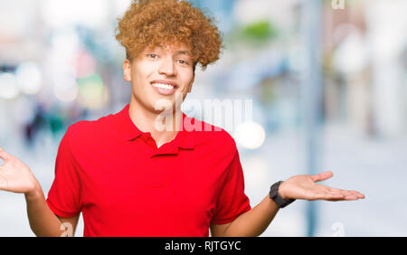Young handsome man with afro hair wearing red t-shirt Smiling showing both hands open palms, presenting and advertising comparison and balance - Stock Photo