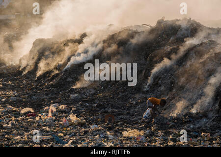 Young child collecting recyclable materials among toxic smoke from rubbish dump in Rishikesh, Uttarakhand, India - Stock Photo