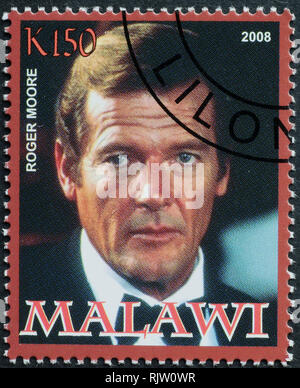 Roger Moore portrait on postage stamp - Stock Photo