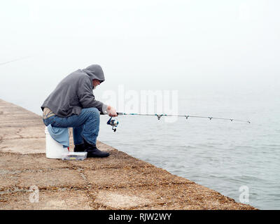 An old man in blue jeans and gray hooded  sweat shirt sits on a five gallon bucket while fishing on a foggy day. South jetty Port Aransas, Texas USA. - Stock Photo