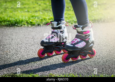 Teenage girl is skating on roller blades in the park  - Stock Photo