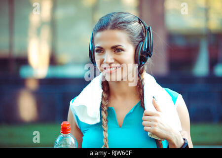 Image of a beautiful strong young sports woman outdoors on urban background with towel on neck listening to music with headphones on head smiling with - Stock Photo