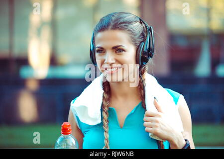 sports woman outdoors on urban background with towel on neck - Stock Photo