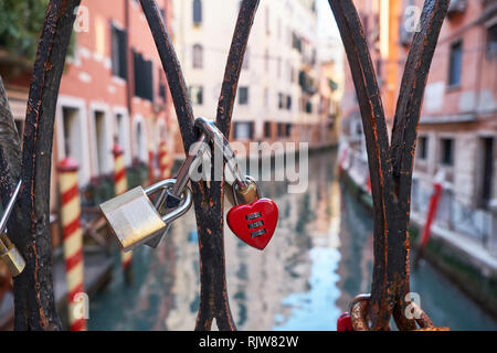 Combination red heart-shaped and other padlocks on the bridge in Venice, Italy. Sunny day, historical buildings and the canal in the background. Close - Stock Photo