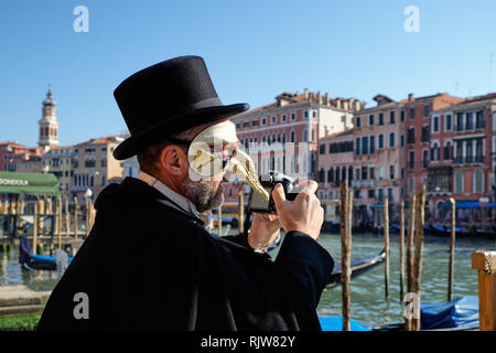 Venice, Italy - February 10, 2018: Man in a pantalone mask on the peer holding a DSLR camera and taking pictures during the Carnival. Gondolas and his - Stock Photo