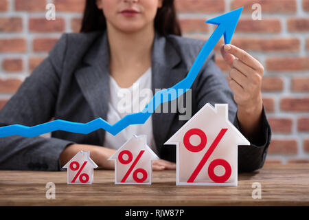 Close-up Of Businesswoman Showing Growth In Real Estate Sitting At Desk Against Brick Wall - Stock Photo