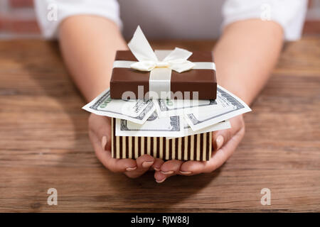 Close-up Of Female's Hand Holding Gift Box Filled With Currency Over The Wooden Desk - Stock Photo