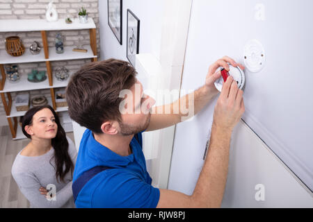 Happy Woman Standing Near Serviceman Replacing Battery In Smoke Alarm - Stock Photo