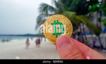 Hand holding golden bitcoin on the beach, on the background of sea wave. Bitcoin is a modern way of exchange this crypto currency is a convenient mean - Stock Photo