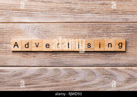 ADVERTISING word written on wood block. ADVERTISING text on wooden table for your desing, concept. - Stock Photo