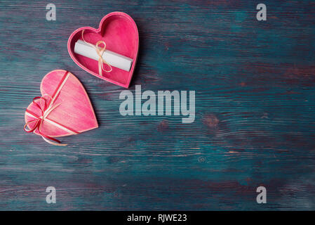 Open heart shaped gift box and love letter on blue wooden background - Stock Photo