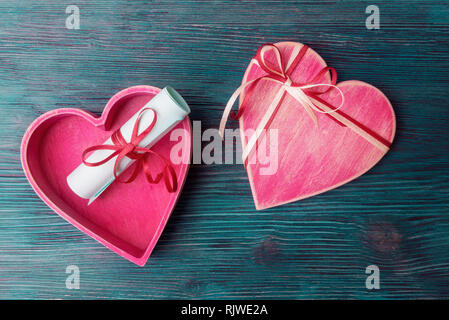 Heart shaped gift box and love letter on blue wooden background - Stock Photo