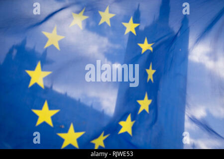 As Prime Minister Theresa May negotiates further Britain's exit from the European Union in Brussels, the UK parliament is seen through the yellow stars of the EU flag, flying as part of an anti-Brexit protest opposite the Houses of Parliament, on 7th February 2019, in Westminster, London England. - Stock Photo