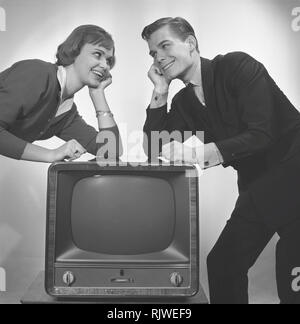 Television in the 1950s. A young couple is pictured beside a typical 50s television set.  Photo Kristoffersson ref CC93-5. Sweden 1958 - Stock Photo
