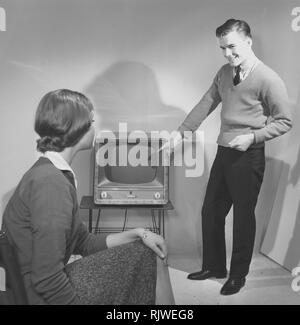 Television in the 1950s. A young couple is pictured with a typical 50s television set.  Photo Kristoffersson ref CC94-2. Sweden 1958 - Stock Photo