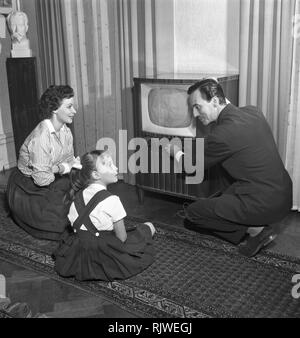 Television in the 1950s. A young couple is pictured with a typical 50s television set. The husband is adjusting the pictures and his wife and child is admiring the modern kind of home entertainment.  Photo Kristoffersson ref BU35-12. Sweden 1950s - Stock Photo