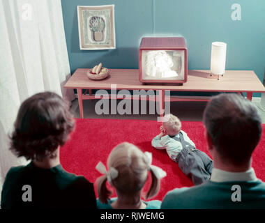 Television in the 1950s. A young couple is pictured in front of a typical 50s television set. The whole family is  admiring the modern kind of home entertainment.  Sweden 1958 - Stock Photo