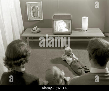 Television in the 1950s. A young couple is pictured in front of a typical 50s television set. The whole family is  admiring the modern kind of home entertainment.  Sweden 1958. ref 3789 - Stock Photo