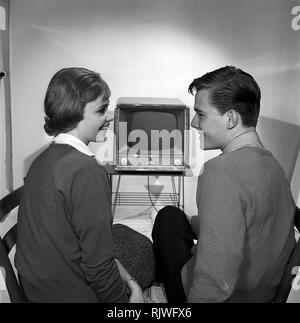 Television in the 1950s. A young couple is pictured in front of a typical 50s television set.  Photo Kristoffersson ref CC93-8. Sweden 1958 - Stock Photo