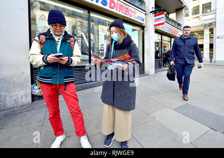 London, England, UK. Japanese tourists, one with a facemask, looking at a map in central London - Stock Photo