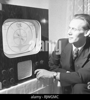 Television in the 1950s. A man with an early television set adjusting the picture. November 1953 - Stock Photo