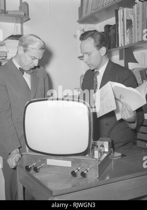 Television in the 1950s. A man with an early television set in production or testing at the Elfo company is experimenting with television technology. January 1954 - Stock Photo
