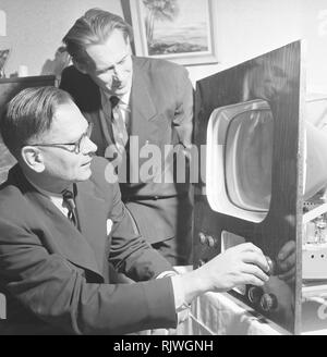 Television in the 1950s. A man with an early television set in production or testing is adjusting the picture. November 1953 - Stock Photo