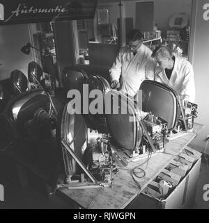 Television in the 1950s. A man with an early television set in production or testing at the Elfo company is experimenting with television technology. November 1959 - Stock Photo