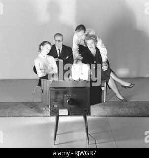 Television in the 1950s. Family in front of a television set and fascinated by the new television medium in March 1959. Sweden - Stock Photo