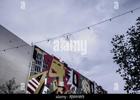 festive lighting across a street with a graffiti wall - Stock Photo