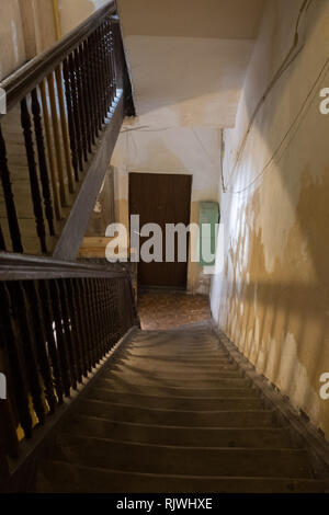 empty staircase in shadow leading down to a door in a tenement house in Warsaw - Stock Photo