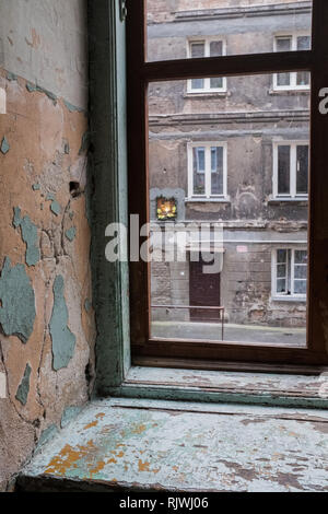 Effigy of the Virgin Mary in a wall in a tenement house in Warsaw,as seen through a window - Stock Photo