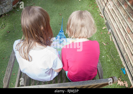 two young girls looking at a book on pop up book of Paris - Stock Photo