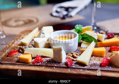 Cheese plate served with grapes, honey and nuts on a wooden background. Various types of cheese - Stock Photo