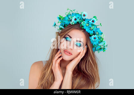 woman posing with flowers on head blue eyeshadow closed eyes - Stock Photo