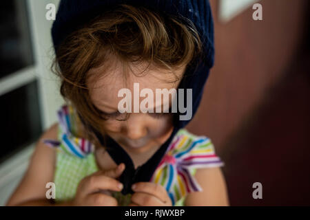 A toddler girl tries to hook her winter hat while standing outside on a warm day. - Stock Photo